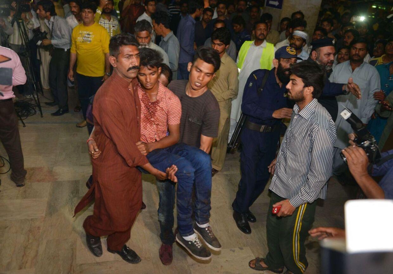 Pårørende hjælpre ofrene frem til et hospital i Lahore i Pakistan. Foto: AFP PHOTO / ARIF ALI.