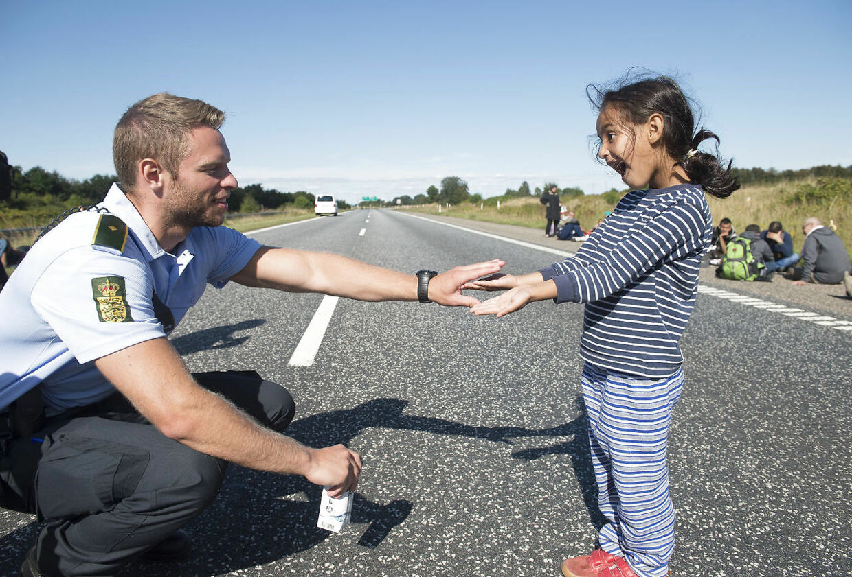 HIGH LIGHT from migrant situation in Denmark eraly September- - A Danish policeman plays with a migrant girl at the E45 freeway north of Padborg 09 September 2015. Migrants, mainly from Syria and Iraq, arrived this morning at Padborg with a train from Germany and were placed at a school in Padborg from where they fled, to try to get to Sweden by walking the freeway. The police closed the freeway for security reasons.