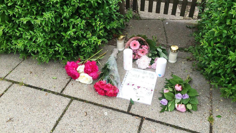 Lys og blomster er lagt foran hjemmet, hvor tragedien udspillede sig.