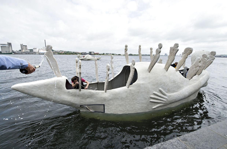 """Lørdag formiddag kom 3 sejlende skulpturbåde i beton , udarbejdet af den norskfødte billedkunstner Marit Benthe Norheim, sejlende fra Nørresundby til Aalborg . Bådene er tredelte portrætter af kvinden i forskellige stadier og tilstande, de er 12 m. lange, eldrevne og måler 3 meter over vandoverfladen. Ved ankomsten til Aalborg blev de navngivet, alle 3 skibes navne begynder med: """"Mit skb er ladet med"""" , her døbes skibet """"Minder"""" , i baggrunden flyder """"Liv"""" . Efter søsætningen lørdag skal de sejle i Limfjorden og langs den østjyske kyst i 2016 og de vil være en del af højdepunkterne i Den Europæiske Kulturhovedstad Aarhus i 2017."""