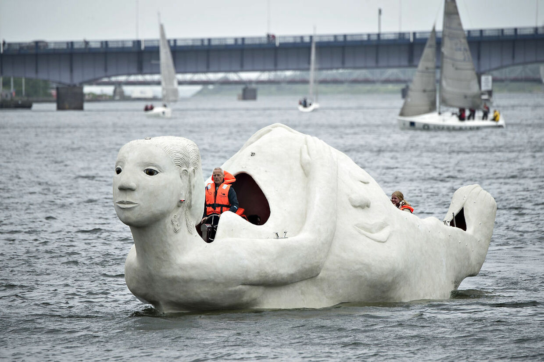 """Lørdag formiddag kom 3 sejlende skulpturbåde i beton , udarbejdet af den norskfødte billedkunstner Marit Benthe Norheim, sejlende fra Nørresundby til Aalborg . Bådene er tredelte portrætter af kvinden i forskellige stadier og tilstande, de er 12 m. lange, eldrevne og måler 3 meter over vandoverfladen. Ved ankomsten til Aalborg blev de navngivet, alle 3 skibes navne begynder med: """"Mit skb er ladet med"""" , her det skibet """"Liv"""" . Efter søsætningen lørdag skal de sejle i Limfjorden og langs den østjyske kyst i 2016 og de vil være en del af højdepunkterne i Den Europæiske Kulturhovedstad Aarhus i 2017.. (Foto: Henning Bagger/Scanpix 2016)"""