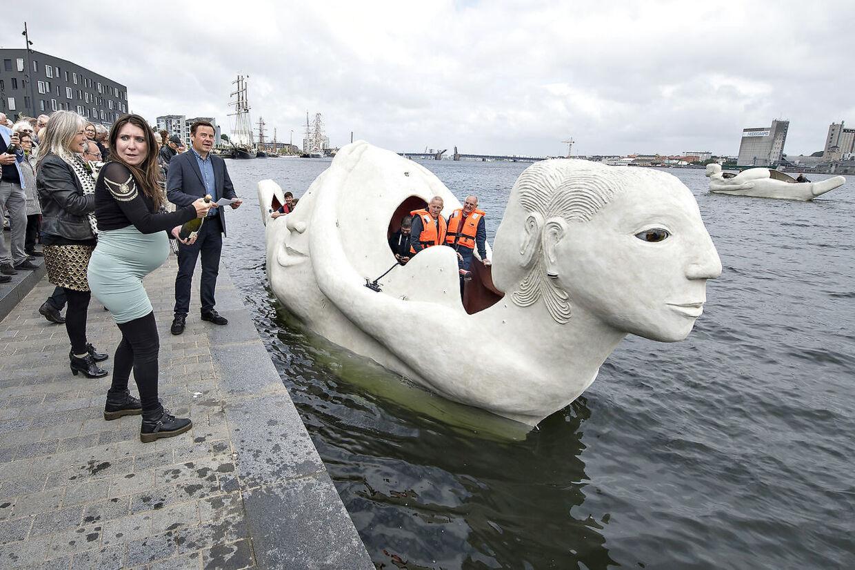 """Lørdag formiddag kom 3 sejlende skulpturbåde i beton , udarbejdet af den norskfødte billedkunstner Marit Benthe Norheim, sejlende fra Nørresundby til Aalborg . Bådene er tredelte portrætter af kvinden i forskellige stadier og tilstande, de er 12 m. lange, eldrevne og måler 3 meter over vandoverfladen. Ved ankomsten til Aalborg blev de navngivet, alle 3 skibes navne begynder med: """"Mit skb er ladet med"""" , her døbes skibet """"Liv"""" af højgravide Inga Gerner Nielsen, tv. kunstneren og bagved Aalborgs borgmester Thomas Kastrup Larsen . Efter søsætningen lørdag skal de sejle i Limfjorden og langs den østjyske kyst i 2016 og de vil være en del af højdepunkterne i Den Europæiske Kulturhovedstad Aarhus i 2017."""