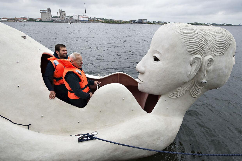 """Lørdag formiddag kom 3 sejlende skulpturbåde i beton , udarbejdet af den norskfødte billedkunstner Marit Benthe Norheim, sejlende fra Nørresundby til Aalborg . Bådene er tredelte portrætter af kvinden i forskellige stadier og tilstande, de er 12 m. lange, eldrevne og måler 3 meter over vandoverfladen. Ved ankomsten til Aalborg blev de navngivet, alle 3 skibes navne begynder med: """"Mit skb er ladet med"""" , her det styrehuset på skibet """"Liv"""" . Efter søsætningen lørdag skal de sejle i Limfjorden og langs den østjyske kyst i 2016 og de vil være en del af højdepunkterne i Den Europæiske Kulturhovedstad Aarhus i 2017.. (Foto: Henning Bagger/Scanpix 2016)"""