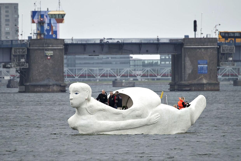 """Lørdag formiddag kom 3 sejlende skulpturbåde i beton , udarbejdet af den norskfødte billedkunstner Marit Benthe Norheim, sejlende fra Nørresundby til Aalborg . Bådene er tredelte portrætter af kvinden i forskellige stadier og tilstande, de er 12 m. lange, eldrevne og måler 3 meter over vandoverfladen. Ved ankomsten til Aalborg blev de navngivet, alle 3 skibes navne begynder med: """"Mit skb er ladet med"""" , her skibet """"Længsel"""" , i baggrunden Limfjordbroen . Efter søsætningen lørdag skal de sejle i Limfjorden og langs den østjyske kyst i 2016 og de vil være en del af højdepunkterne i Den Europæiske Kulturhovedstad Aarhus i 2017."""