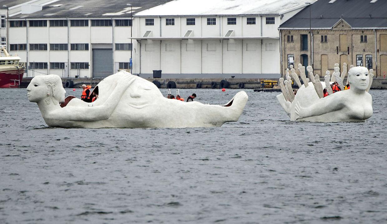 """Lørdag formiddag kom 3 sejlende skulpturbåde i beton , udarbejdet af den norskfødte billedkunstner Marit Benthe Norheim, sejlende fra Nørresundby til Aalborg . Bådene er tredelte portrætter af kvinden i forskellige stadier og tilstande, de er 12 m. lange, eldrevne og måler 3 meter over vandoverfladen. Ved ankomsten til Aalborg blev de navngivet, alle 3 skibes navne begynder med: """"Mit skb er ladet med"""" , her skibene """"Liv"""" (tv) og """"Minder"""" . Efter søsætningen lørdag skal de sejle i Limfjorden og langs den østjyske kyst i 2016 og de vil være en del af højdepunkterne i Den Europæiske Kulturhovedstad Aarhus i 2017."""