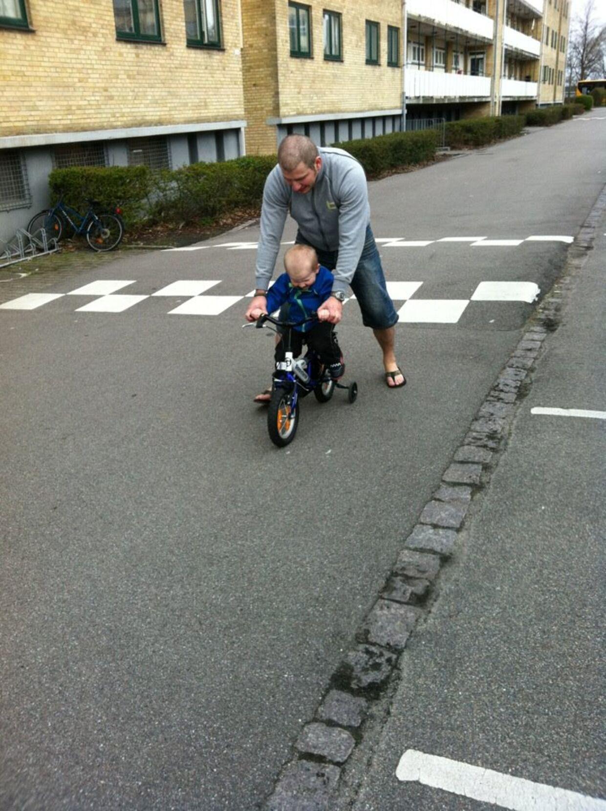 To-årige Maximilian får hjælp af far til at lære at cykle. Billedet er fra april 2012. (Foto: privat)