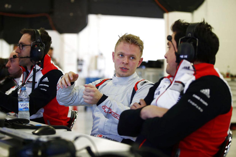En svedig Kevin Magnussen snakker med Porsche-ingeniørerne efter at have kørt.