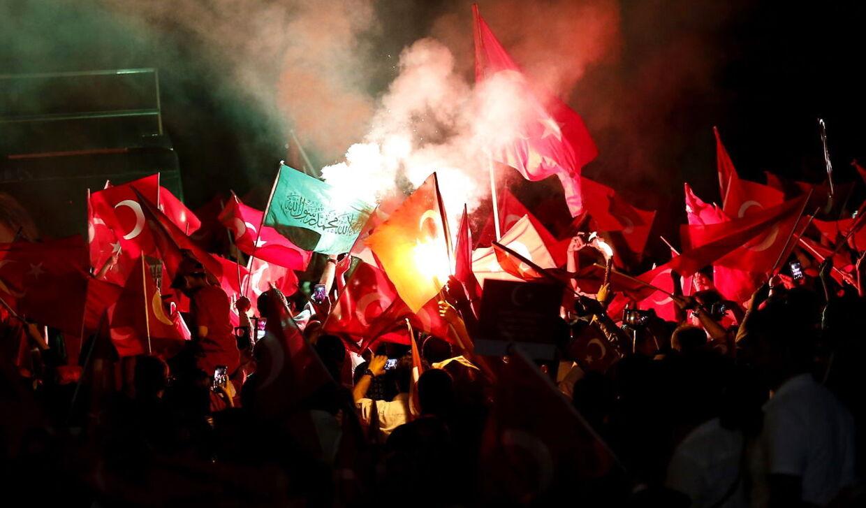 Her holder demonstranter det tyrkiske flag i vejret på Taksim Square i Istanbul 18. juli 2016