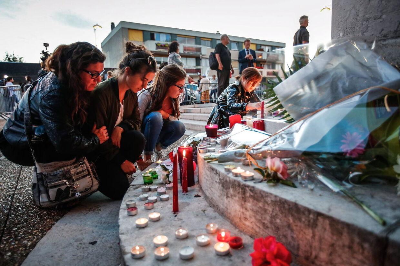Sørgende ved rådhuset i den franske by Saint-Etienne-du-Rouvray, hvor to mænd tirsdag trængte ind i en kirke og dræbte en præst og sårede to nonner under et gidseldrama.