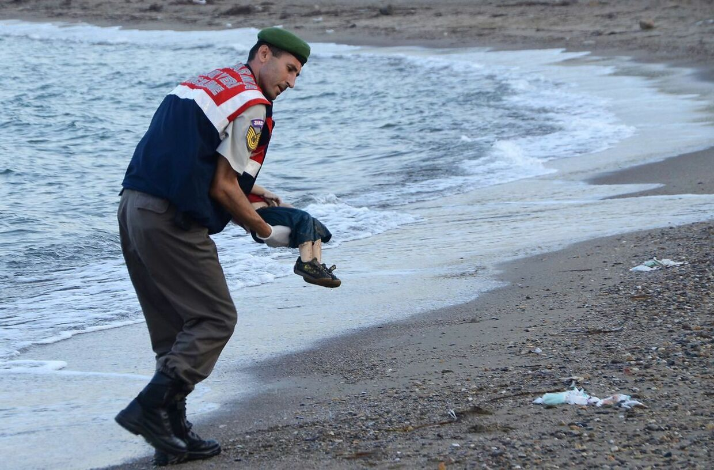 En tyrkisk betjent bærer Aylan Kurdi væk fra stranden nær Bodrum i Tyrkiet.