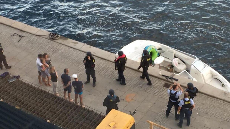 De seks ombordværende i speedbåden blev grundigt bevogtet af de bevæbnede politifolk, efter at de var blevet stoppet på vandet med et varselsskud. Speedbådens kaptajn blev siden sigtet for at have truet politifolkene med den softgun-riffel, der på billedet ligger på kajen.