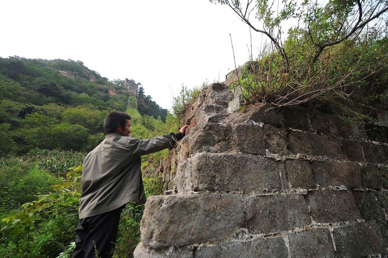 Sådan ser den urestaurerede del af Den Kinesiske Mur ud. En lokal indbygger ved en del af muren, som ikke har været gennem en restaurering.