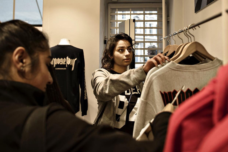 Amina griber fat i en grå sweatshirt på vej over mod stativerne, hvor den trøje, som hun har udset sig, hænger.