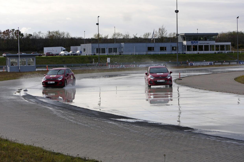 Her tager de to biler en kurve med godt 60 km/t. Sommerbilen til venstre kan slet ikke få vejgreb, og er på vej ud i »grøften«, mens vinterbilen ingen problemer har med at komme rundt.
