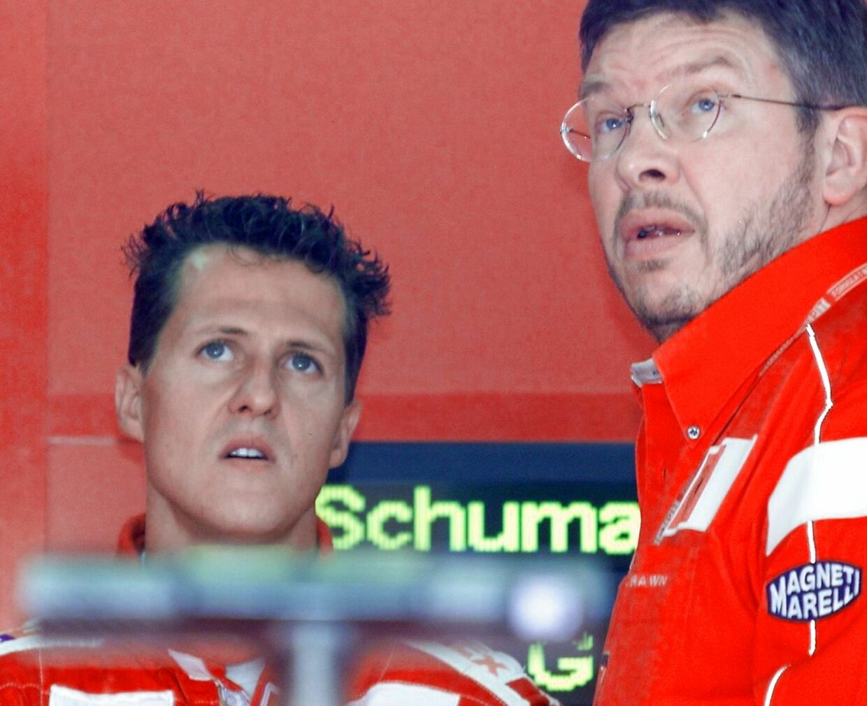 German Ferrari driver Michael schumacher (L) and his technical director Ross Brawn watch TV screen 30 June 2000 in the pits of the Magny-Cours racetrack, during the first free practice session, two days before the 86th French Formula One Grand Prix. (ELECTRONIC IMAGE) AFP PHOTO SAMIRA BOUHIN