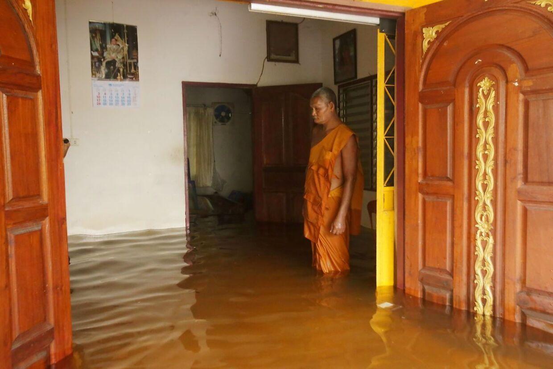 En thailandsk munk står i døren ind til et oversvømmet bhudistisk tempel nær Nakorn Sri Thammarat.