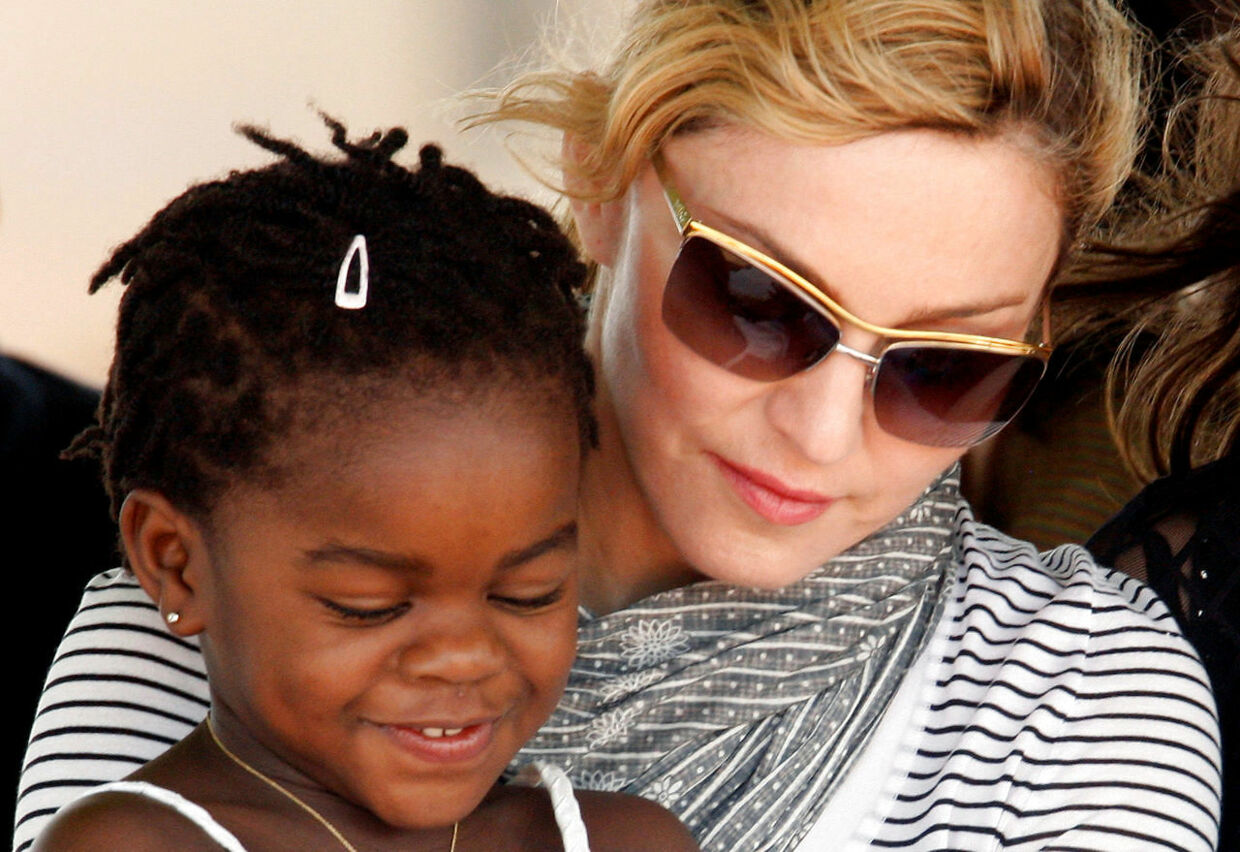 FILE PHOTO: Pop star Madonna sits with her adopted Malawian child Mercy James during a bricklaying ceremony at the site of her Raising Malawi Girls Academy, near the capital Lilongwe, Malawi, April 6, 2010. REUTERS/Mike Hutchings/File Photo
