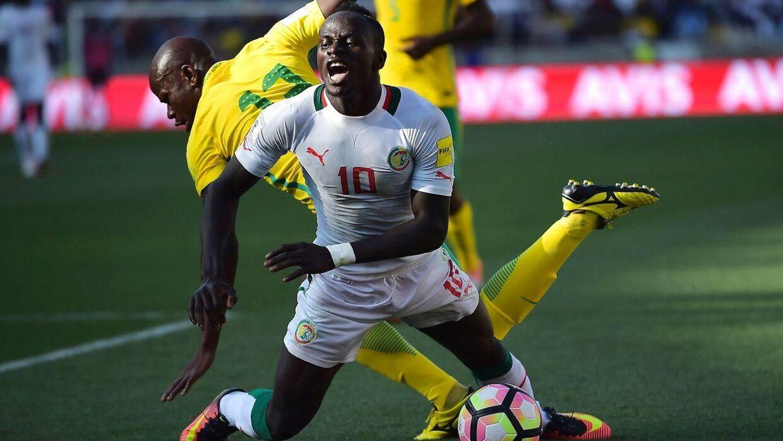 Sydafrikas Hlompho Kekana (tv) tackler Senegals Sadio Mané under VM-kvalifikationskampen i november sidste år. Det var dog ikke denne situation, som førte til straffespark.