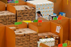 "(FILES) This file photo taken on November 28, 2013 shows an employee collects orders at the Fulfilment Centre for online retail giant Amazon in Peterborough, central England. US tech and retail giant Amazon on February 20, 2017, said it would create 5, 000 British jobs this year, in a show of confidence in the UK economy ahead of Brexit. ""Amazon UK today announced plans to create more than 5, 000 full-time jobs this year, taking the company's total UK workforce to over 24, 000, "" a statement said. / AFP PHOTO / Andrew YATES"