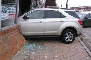 Her ses kørelærens bil halvvejs inde i hendes køreskole.