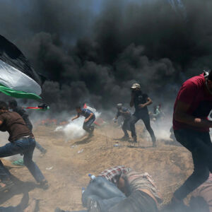 Palestinian demonstrators run for cover from Israeli fire and tear gas during a protest against U.S. embassy move to Jerusalem and ahead of the 70th anniversary of Nakba, at the Israel-Gaza border in the southern Gaza Strip May 14, 2018. REUTERS/Ibraheem Abu Mustafa TPX IMAGES OF THE DAY
