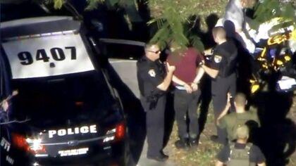 Den formodede gerningsmand bliver fastholdt af politiet nær Marjory Stoneman Douglas High School efter skoleskyderiet i Parkland, Florida.