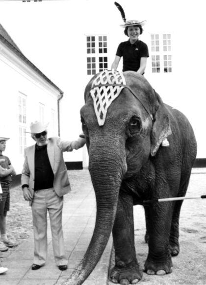 Mange danskere har været en tur i Cirkus Benneweis. Således også kongefamilien. Her ses en ung kronprins Frederik, da han i Graasten fik en tur på en af cirkuselefanterne. Det er Eli Benneweis, der står ved elefanten.