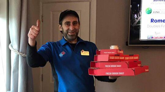 Her er bestillingen og tommelen op! Et glad bud har leveret pizzaerne ved fodenden af sengen.