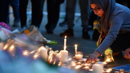 En ung britisk kvinde tænder et lys for de, der mistede livet mandag aften foran Manchester Arena.