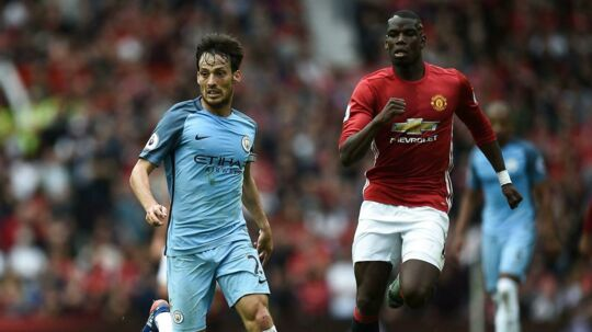 De to Manchester-klubber er forenet i ønsket om at hjælpe familier til ofrene for mandagens bombeangreb i Manchester. Her er det David Silva (tv) for Manchester City og Paul Pogba for Manchester United.