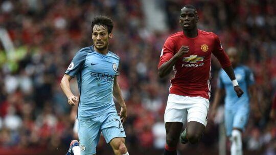 De to Manchester-klubber er forenet i ønsket om at hjælpe familier til ofrene for mandagens bombeangreb i Manchester. Her er det David Silva (tv) for Manchester City og Paul Pogba for Manchester United.