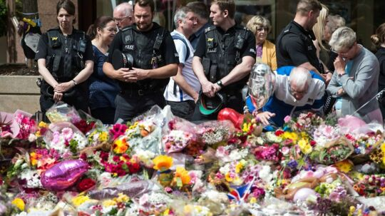 Police officers join members of the public to view the flowers and messages of support in St Ann's Square in Manchester, northwest England on May 31, 2017, placed in tribute to the victims of the May 22 terror attack at the Manchester Arena. / AFP PHOTO / OLI SCARFF