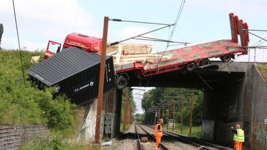 En lastbil er torsdag eftermiddag kørt ud over en togbro og har revet køreledningerne til sporet over.
