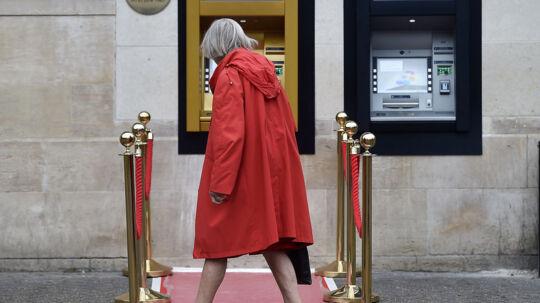 En kvinde går forbi verdens første ATM, der blev sat op uden for Barclays bank i Enfield, den 27. juli 1967.