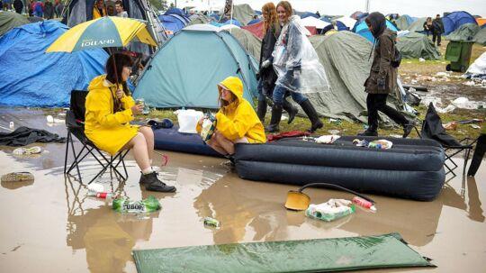 Et par festivaldeltagere hygger sig en stor vandpyt på årets Roskilde Festival.