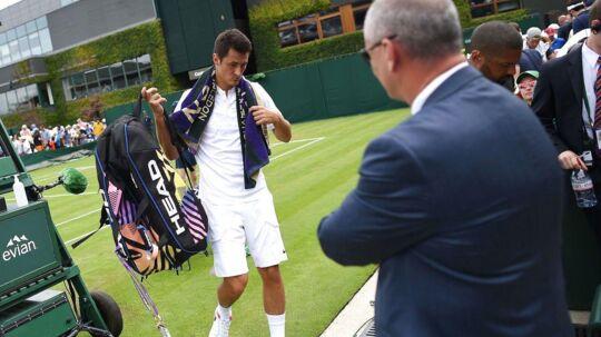 Bernard Tomic tog sig en skadespause i en Wimbledon-kamp, selvom han ikke var skadet. Her foralder han banen efter nederlaget til Mischa Zverev.