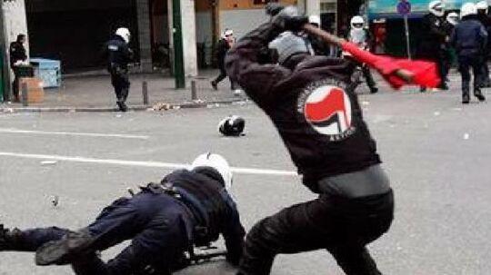 Dette billede er en forfalskning. Logoet på trøjen er lagt ind længe efter billedet først blev publiceret efter en demonstration i Athen i 2009.