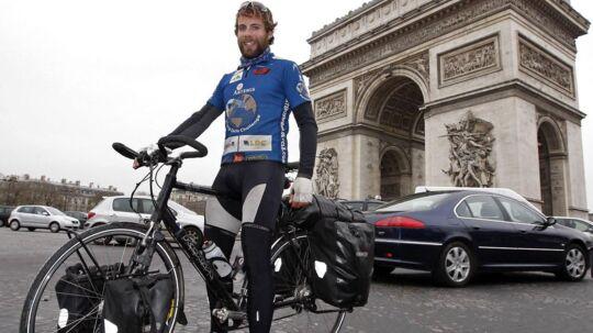 I 2008 var Mark Beaumont 195 dage om at cykle jorden rundt. Her poserer han foran tiumfbuen.