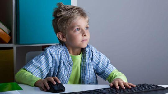 Modelfoto. Dreng er dybt optaget af et computerspil.