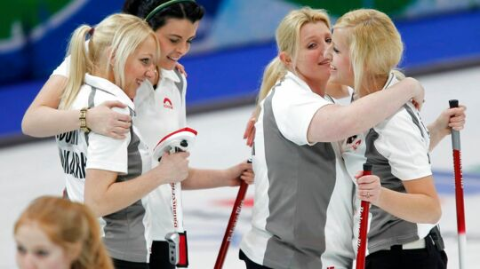 Denmark's fourth Madeleine Dupont (R), skip Angelina Jensen (2nd R), lead Camilla Jensen (C) and third Denise Dupont (2nd L) celebrate victory as Germany's lead Stella Heiss (L) walks past following their women's round robin curling game at the Vancouver 2010 Winter Olympics February 21, 2010. REUTERS/Lyle Stafford (CANADA)