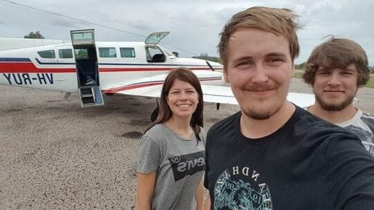 Alexander Philip Jensen (i forgrunden) med sin forlovede Julie Leland (tv) og vennen Nikolaj Nielsen (th) foran det fly, der skaffede dem ud af landsbyen, de endte i efter deres ulykke.