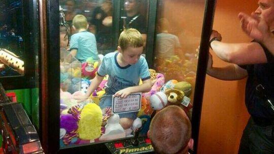 En lille dreng fra USA sad fast i en klomaskine for at få fat i en bamse.
