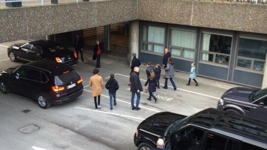 Dronning Margrethe i sort frakke og rød trøje under afventer resten af kongefamilien.