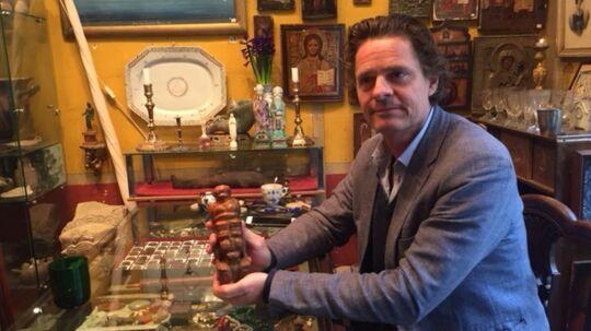 Oliver Klitgaard, der er nær ven med prins Henrik, i sin butik i Indre by i København, hvor Prinsen var en jævnlig gæst, når han skulle købe nye antikvariske jadefigurer fra Asien. På billedet viser antikvitetshandleren en figur frem, som han typisk ville vise til sin ven