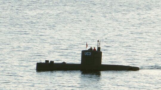 """(FILES) This file photo taken on August 10, 2017 shows a man and a woman standing in the tower of the private submarine """"UC3 Nautilus"""" in Copenhagen Harbor. The trial of Danish submarine builder Peter Madsen, charged with murdering and mutilating Swedish journalist Kim Wall, resumes on March 21, 2018 as prosecutors are not convinced by his account that she died in an accident on board his vessel. / AFP PHOTO / Peter THOMPSON"""