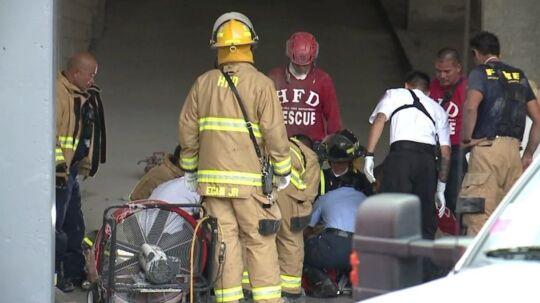 Brandmænd der er i gang med at behandle den 55-årige mand, der var fastklemt melle to bygninger. Foto: KHON-TV