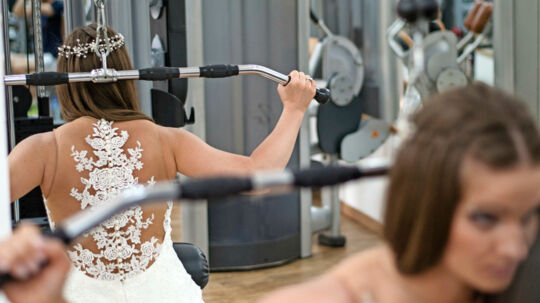 Young Woman Wearing A Bridal Dress And Exercising, Doing Shoulder And Upper Back Exercises At The Gym - Training For/Before Marriage, Preparing For Marriage Concept