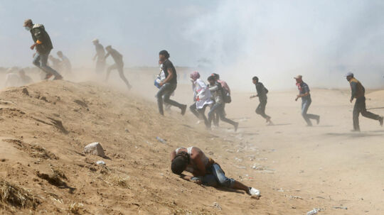 A Palestinian demonstrator reacts as others run from tear gas fired by Israeli forces during a protest marking the 70th anniversary of Nakba, at the Israel-Gaza border in the southern Gaza Strip May 15, 2018. REUTERS/Ibraheem Abu Mustafa TPX IMAGES OF THE DAY