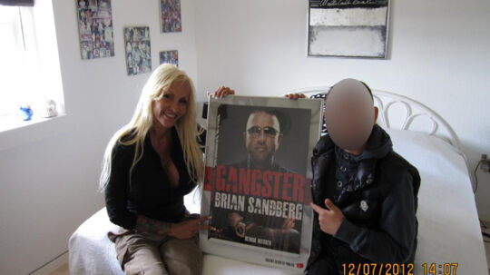 """Linse Kessler og Brian Sandbergs søn poserer blandt andet med en indrammet forside af Brian Sandbergs nye bog, """"Gangster"""" i mellem sig."""