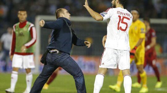 Albaniens Mergim Mavraj forsøger at stoppe en serbisk fan i at slå ham.